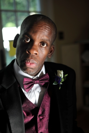 Photo of Black man in dapper tuxedo looking at camera.